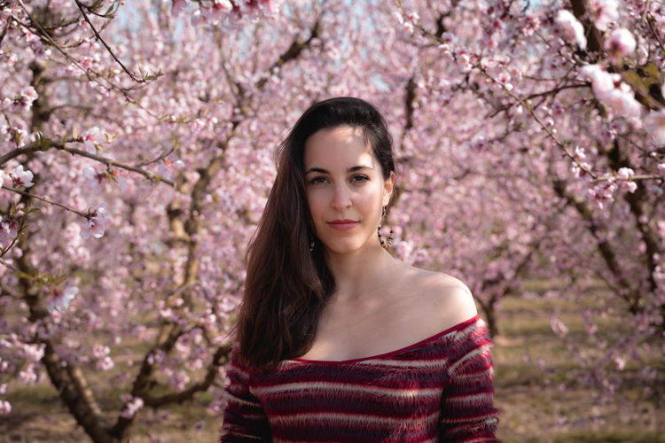 Portrait of beautiful young woman standing by cherry blossom tree