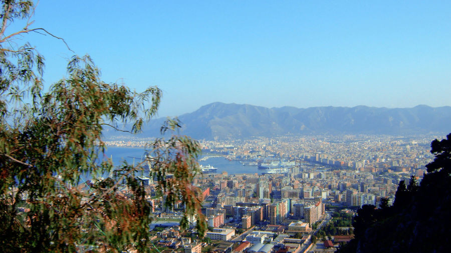 Panoramic view of townscape and mountains against clear blue sky