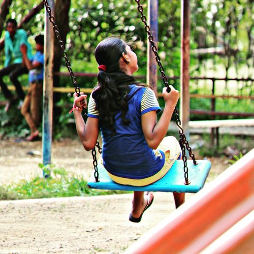 Rear view of girl swinging at playground