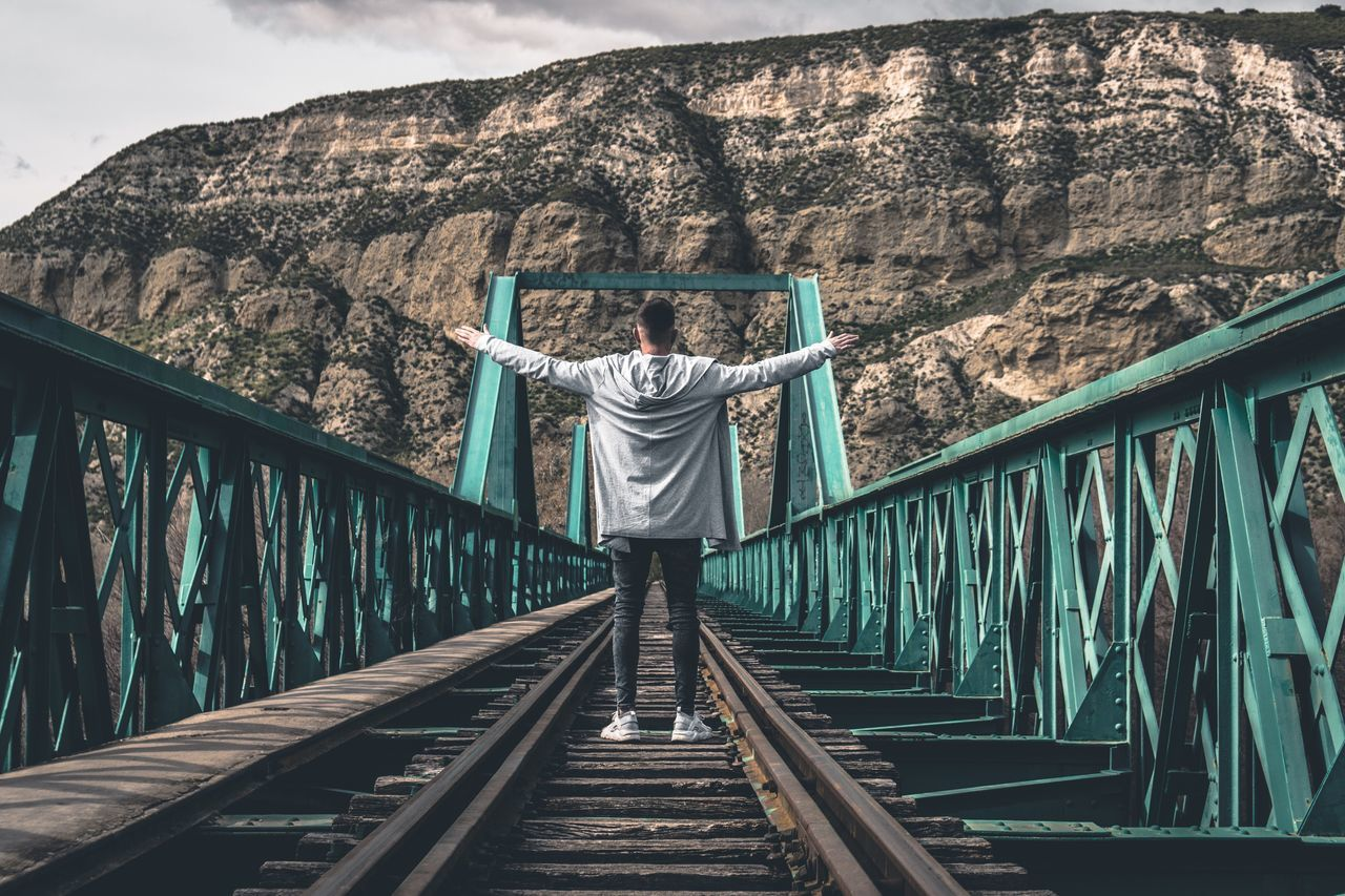 Man Standing On Bridge Against Sky