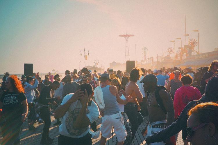 People Dancing On Floor At Coney Island Against Sky