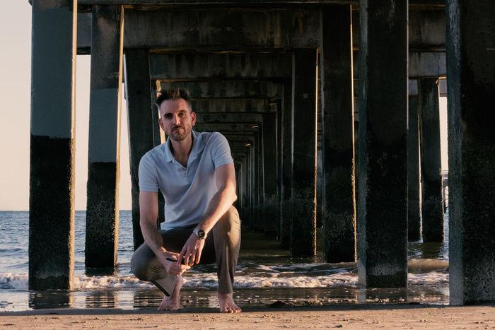 Man Neleen under a beach pier at sunset Sandy Batefoot Vacation Travel Pier Beach Kneeling Man