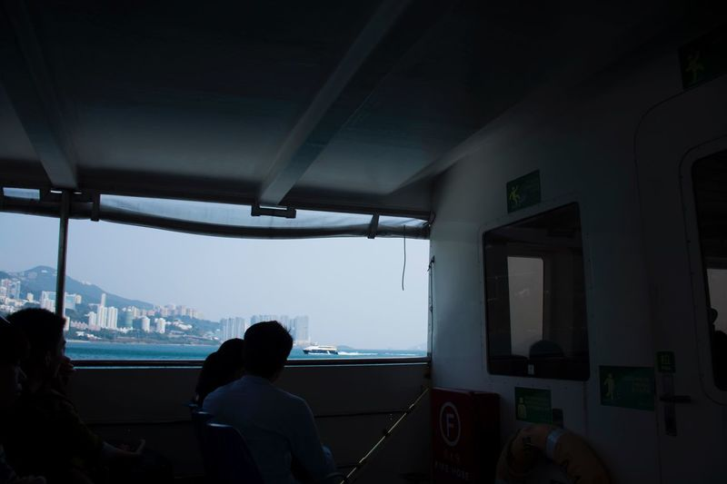 Real People Indoors  Window Built Structure Rear View Architecture Leisure Activity Two People Women Lifestyles Looking Through Window Men Sitting Illuminated City Sky Sea Building Exterior Nautical Vessel Day