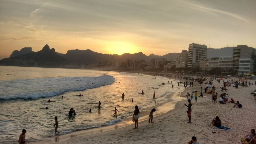 Panoramic view of people on beach against sky during sunset