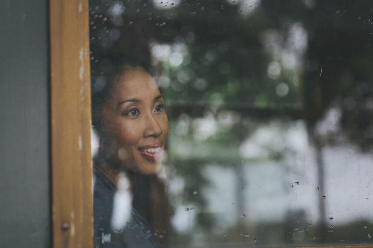 Young woman seen through glass window
