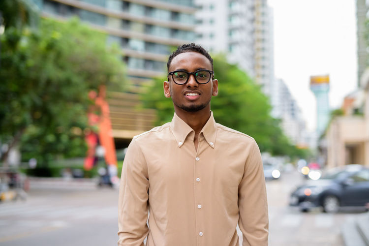 Portrait of smiling young man standing on street