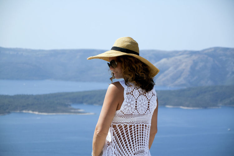Woman wearing hat standing by sea against sky
