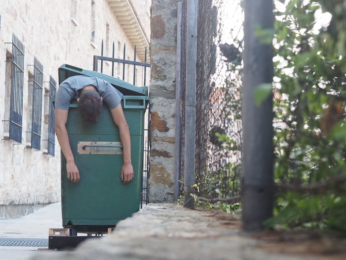 Homeless man sleeping in garbage bin