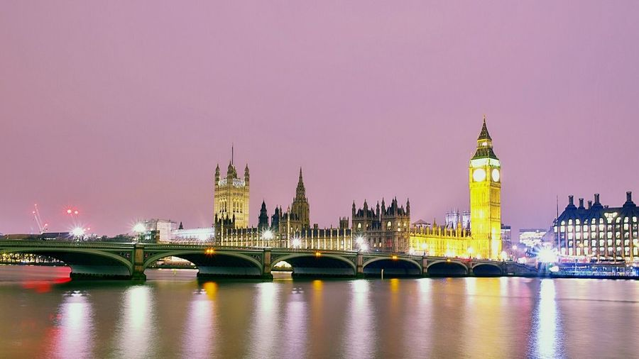 Scenic view of thames river by illuminated houses of parliament and westminster bridge against clear sky