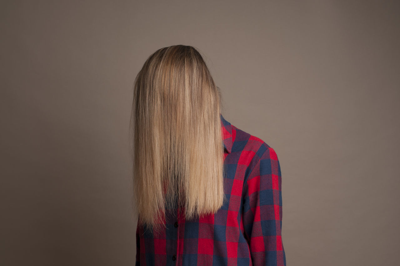 Woman covering face with hair against brown background