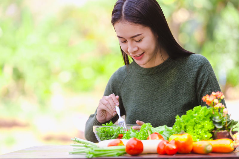 Young woman holding food outdoors