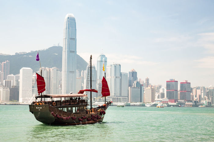Traditional Chinese junk sailing against the backdrop of modern Hong Kong in Victoria Harbour. Chinese Junk Hong Kong Aqualuna Architecture Bay Building Built Structure Chinese City Cityscape Financial District  Modern Nautical Vessel No People Office Office Building Exterior Outdoors Sea Sky Skyscraper Tower Transportation Urban Skyline Water Waterfront