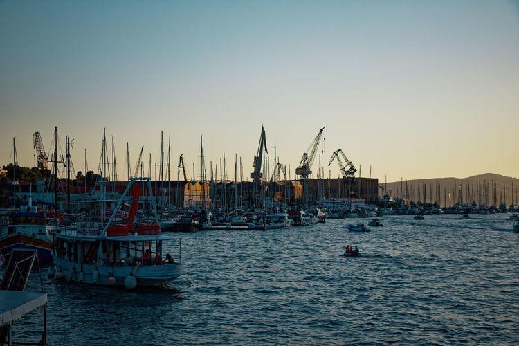 Sailboats in marina at harbor against clear sky