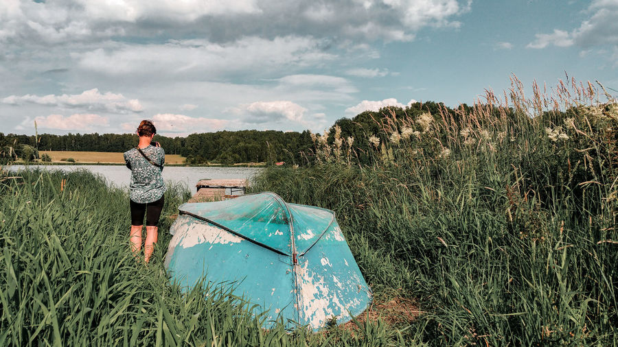taking pictures of the lake, by a turquoise upturned boat Grass Tall Grass Countryside Rural Scene Moscow Region Russia Young Woman Photographer Taking Photos Boat Lake Summer Reeds Jetty Upturned Upturned Boat Turquoise Colored Nature Teenager