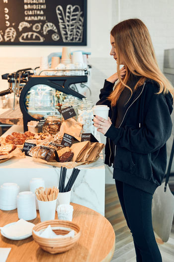 Woman standing with text on table at cafe