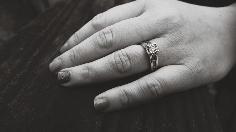 Close-up of woman showing off ring on table