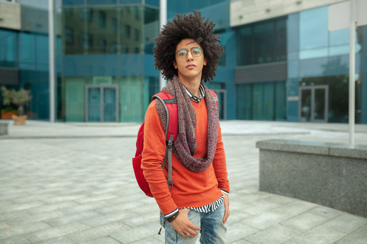 Portrait Of Young Man With Frizzy Hair Standing On Footpath