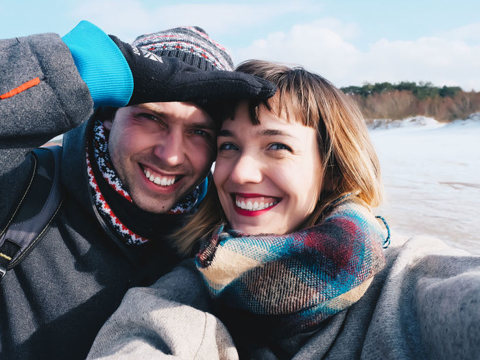 Close-Up Portrait Of Cheerful Young Couple Against Sea