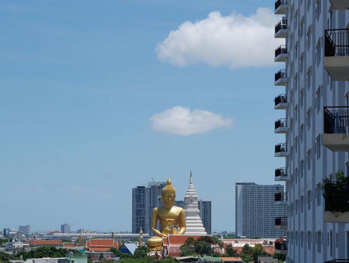 Statue of buildings in city against sky