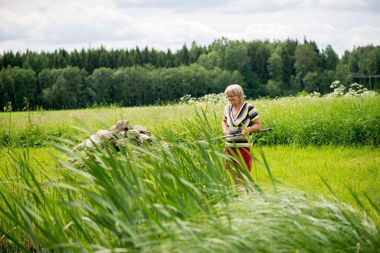 Senior woman standing on grassy field against sky
