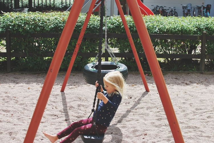 Happy girl swinging on swing at playground