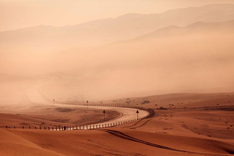 Winding empty road in the desert in fog