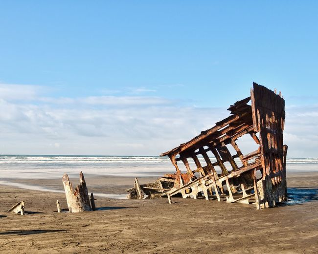 Wooden structure on beach against sky