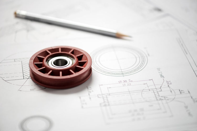 Plastic wheel bearing and grey pencil over blueprint with project drawings, close-up shot from high angle Wheel Architecture Bearing Blueprint Concept Design Drawing Engineering Geometric Shape Pencil Plan Plastic Project Technical Technology Whatman
