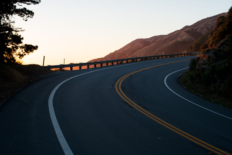 Empty road by mountain against clear sky