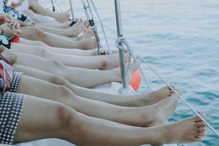 Low section of women sitting on sailboat in sea