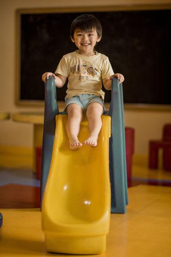 Portrait of smiling boy sitting on slide