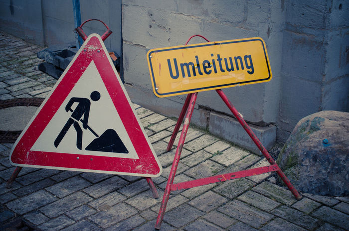 Construction signs City Life Cobblestone Streets Construction Site German Language Signs Street Life Umleitung Architecture Built Structure Close-up Communication Danger Day Guidance Human Representation Information Medium No People Outdoors Road Sign Safety Symbol Text Village Life Warning Warning Sign Yellow
