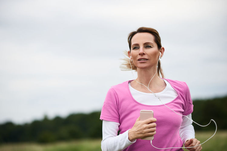 Concentrated sporty woman running in the fields Listening Music Nature Running Trail Running Woman Best Ager Cardio Cross-country Day Exercising Fit Healthy Lifestyle Jogging Leisure Activity Lifestyles Middle-aged One Person Outdoor Outdoors Sports Sports Clothing