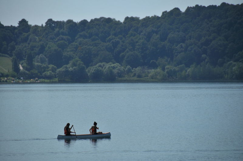 Rear View Of People Canoeing In Lake