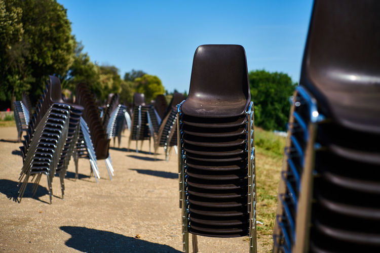 Stacks of chairs on sunny day outdoors