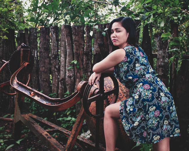 Portrait of young woman standing by rusty old machine in forest