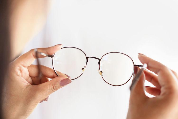 Woman hand hand holding eyeglasses closeup