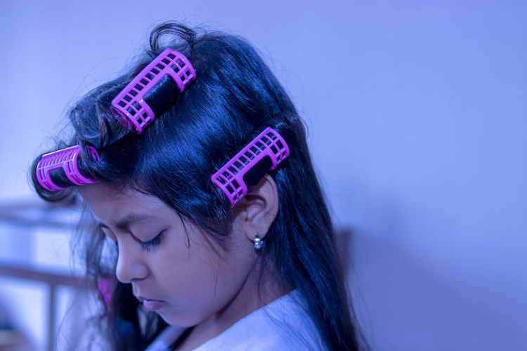 Close-Up Of Girl With Hair Curlers At Home
