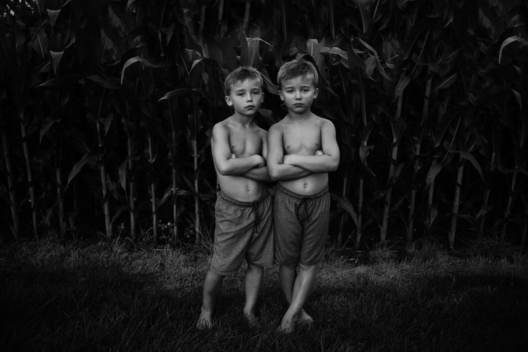 Portrait of shirtless boys standing with arms crossed