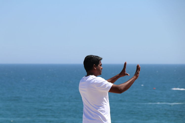 Rear view of mid adult man gesturing while standing at beach against sky