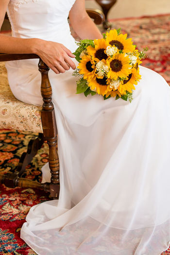 Low section of bride with bouquet sitting on chair at home during wedding ceremony