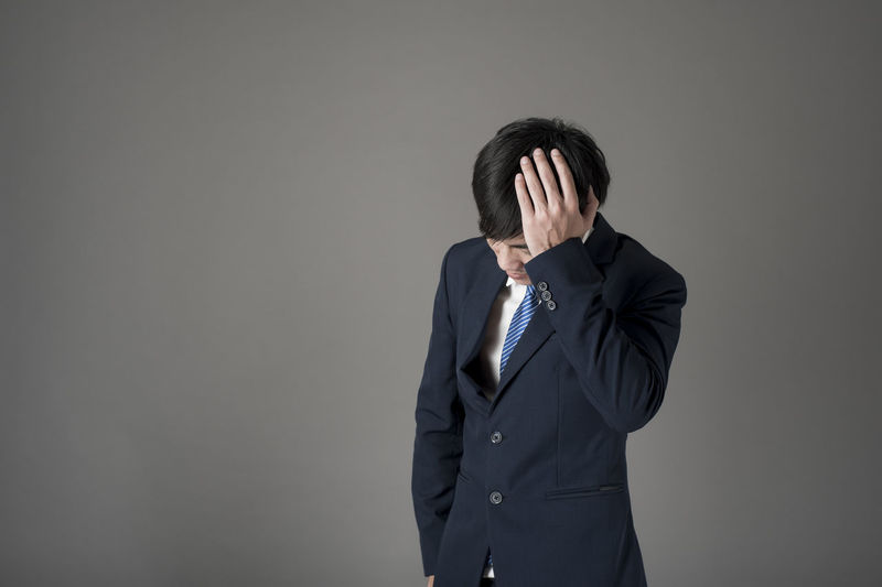 Stressed businessman standing against gray background