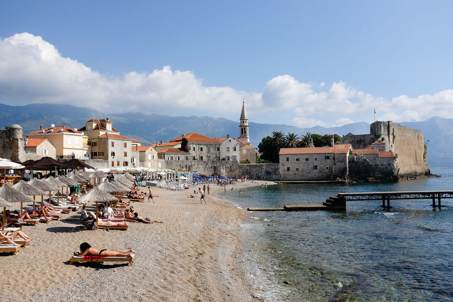 Sunbathers on the beach at Budva Budva Mediterranean  Adriatic Coast Architecture Beach Building Exterior Built Structure Cloud - Sky Coastal Town Day Montenegro Nature Outdoors People Real People Sand Sea Sky Sunbathers Travel Destinations Vacations Water