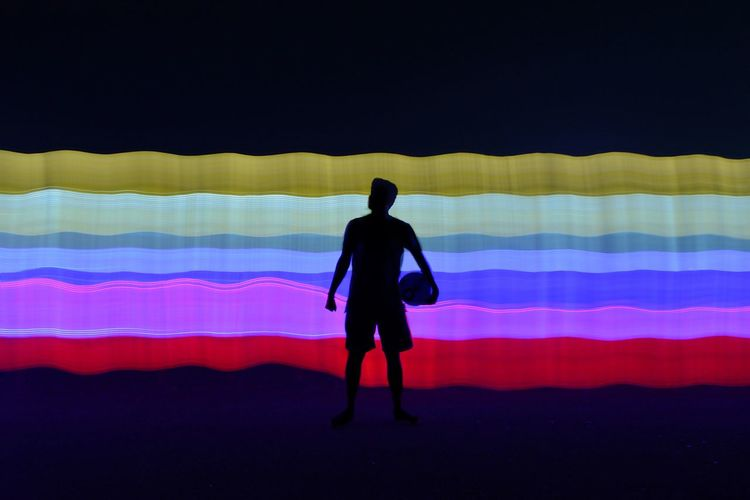 Rear view of silhouette man standing against multi colored umbrella