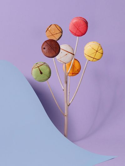 High angle view of colorful macaroons with sticks and paper on purple background