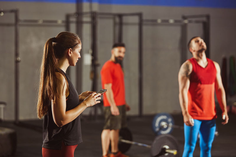 Woman using mobile phone while standing at gym