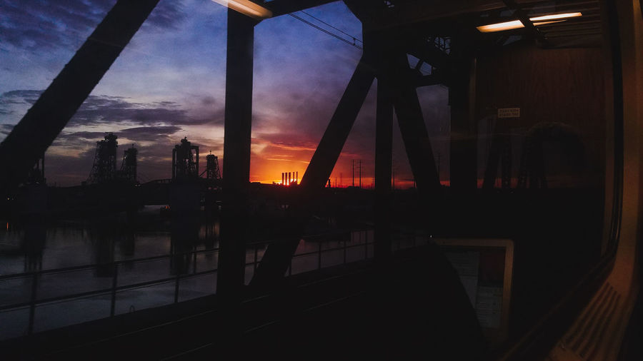 Silhouette of city at sunset seen through window