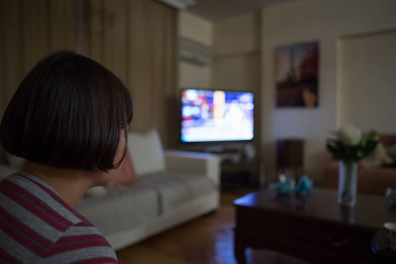 Close-Up Of Girl Watching Tv At Home