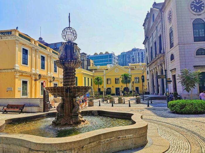 Fountain amidst buildings in city against sky