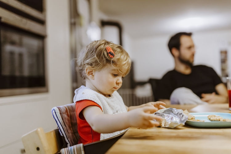Baby girl unwrapping cookies with father in background – Kempen, Germany Baby Chair Cookies Eating Family Family❤ Food And Drink Man Sitting Babygirl Babyhood Candy Close-up Dining Table Father Germany High Chair Holding Home Interior Indoors  Kitchen Side View Table Two People Waist Up